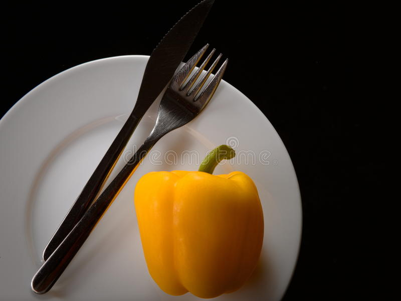 Yellow pepper on a plate with cutlery. Simple image of a yellow pepper on a white plate with cutlery stock photography