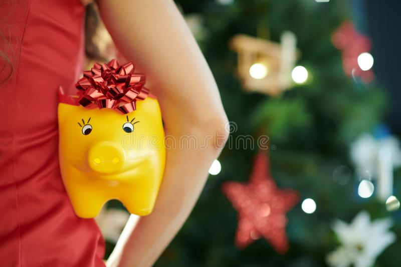 Woman near Christmas tree holded by woman. Yellow piggy bank with red bow in hand of woman in red dress near Christmas tree holded by woman stock images