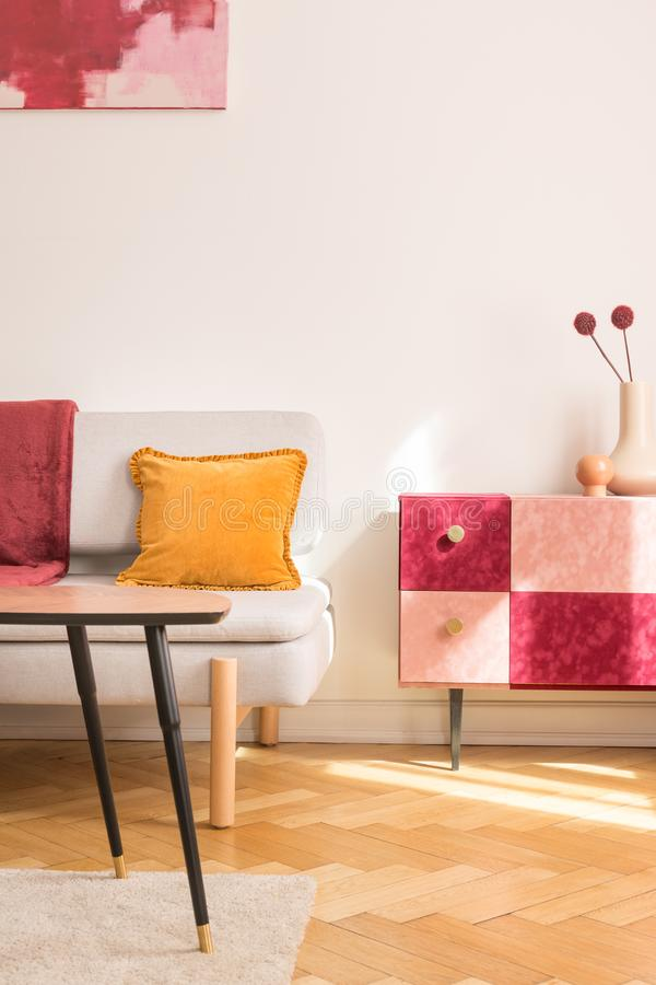 Yellow pillow on sofa next to red and pink cupboard with flowers in flat interior with table. Real photo. Yellow pillow on sofa next to red and pink cupboard royalty free stock photography