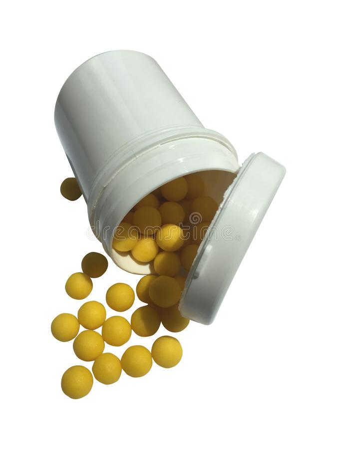Yellow pills spill put of the bottle. Close up background stock photography