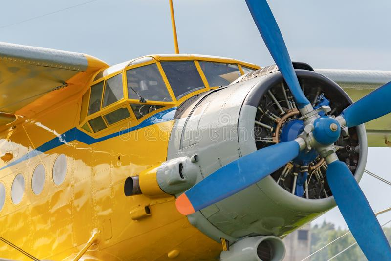 Yellow pilots cabin and engine with blue four blade propeller of soviet aircraft biplane Antonov AN-2 closeup stock photography