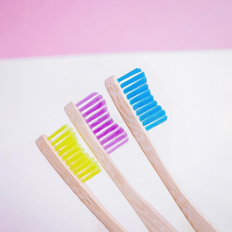 Yellow, pink and blue bamboo toothbrushes. Eco-friendly concept. Minimal, white background. Copy space royalty free stock photography