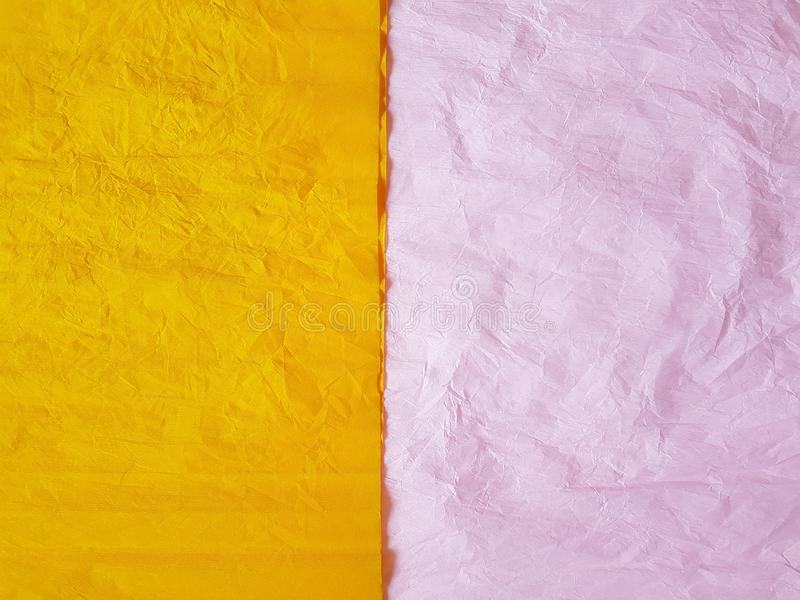 Yellow pink paper background silk surface empty blank sheets vivid colors. Wrapping royalty free stock photography