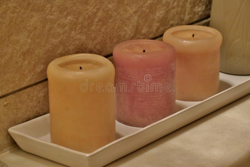 Yellow and pink scented candles on a white stand close-up royalty free stock image