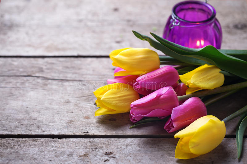 Yellow and pink spring tulips and violet candle on vintage wood stock photography