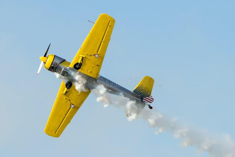 Yellow plane doing turns while sending smoke royalty free stock photography