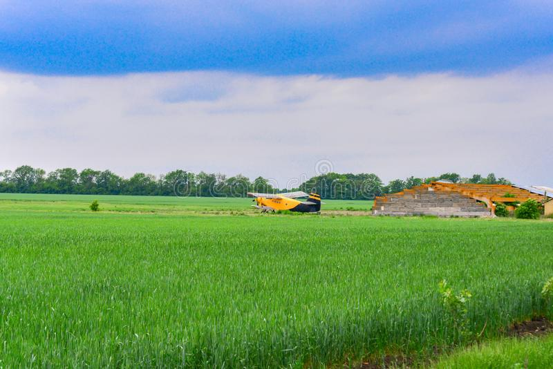 Yellow plane on a wheat field. Sowing, reaping, fertilizer of agricultural crops.  stock image