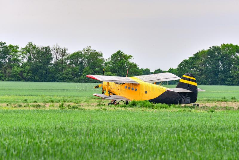 Yellow plane on a wheat field. Sowing, reaping, fertilizer of agricultural crops.  royalty free stock photo