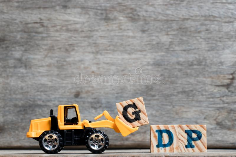 Yellow plastic bulldozer hold letter G to complete word GDP Abbreviation of Gross Dometsic Product or Good Distribution Practice. On wood background stock images
