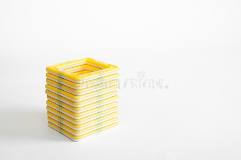 Yellow plastic children`s designer with magnets. On white background. Triangles and squares stock photo