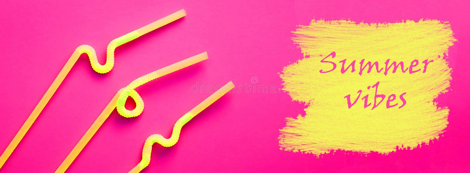 Yellow plastic cocktail tubes with a flexible part, due to which they can be twisted into a knot or in a zigzag, on a crimson back royalty free stock image