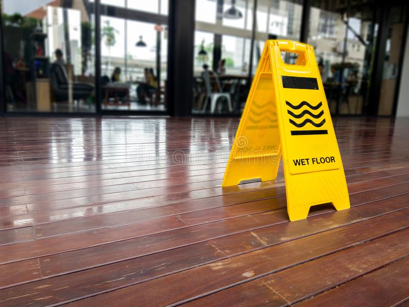 Yellow plastic cone with sign showing warning of wet floor in restaurant. stock image