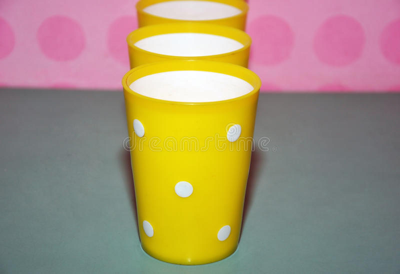 Yellow plastic cups. With white dots royalty free stock photos