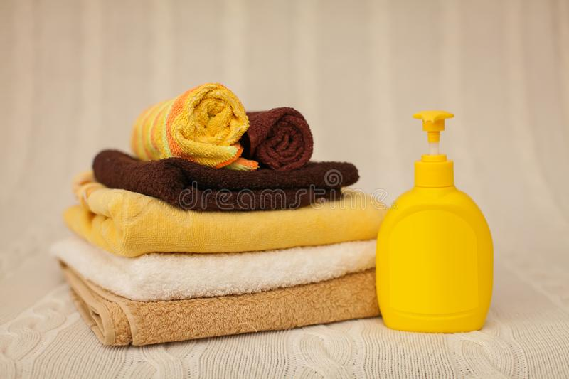 Yellow plastic dispenser with liquid soap and a stack of brown towels on a beige rug in selective focus stock image