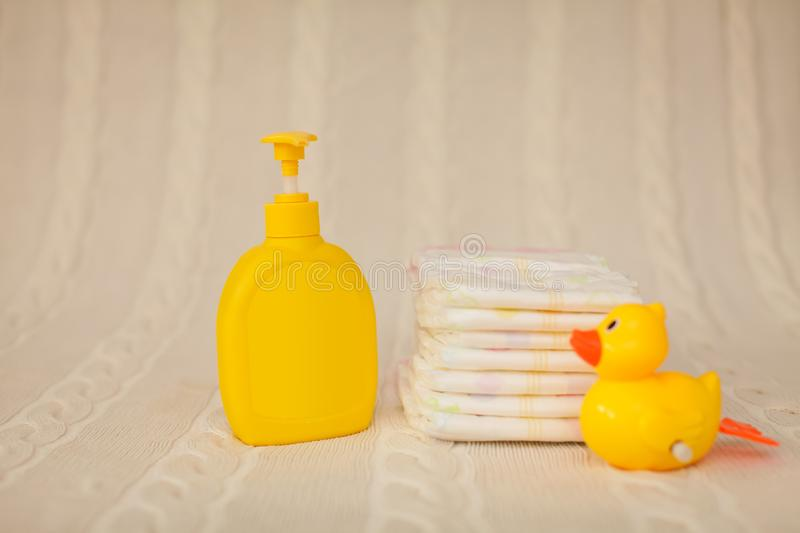 Yellow plastic dispenser with liquid soap and a stack of brown towels on a beige rug in selective focus royalty free stock images