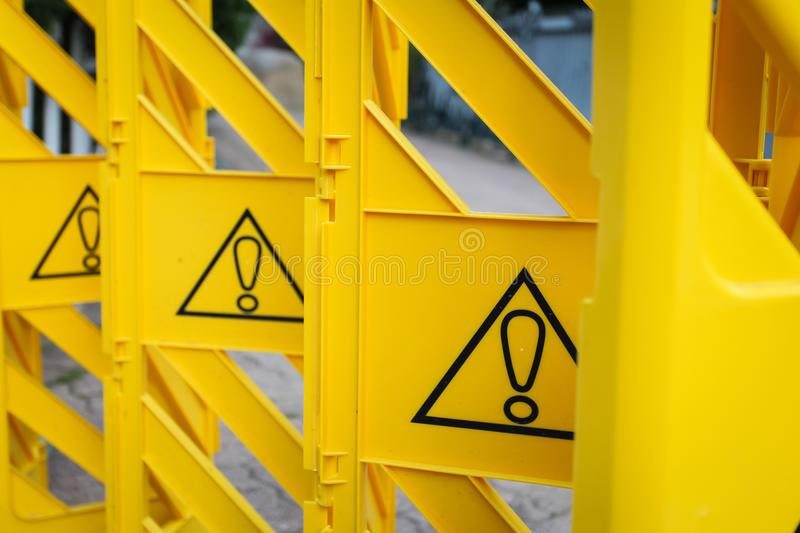 Yellow plastic fence with exclamation marks, concept of prohibition, pay attention stock images