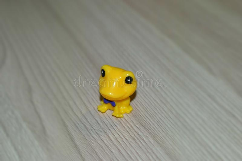 Yellow plastic frog in a tie. stock photo