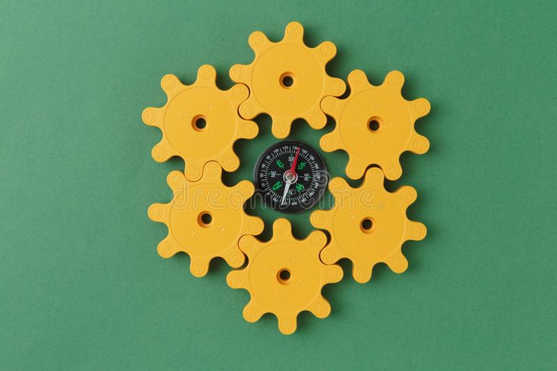 yellow plastic gears and compass stock photos