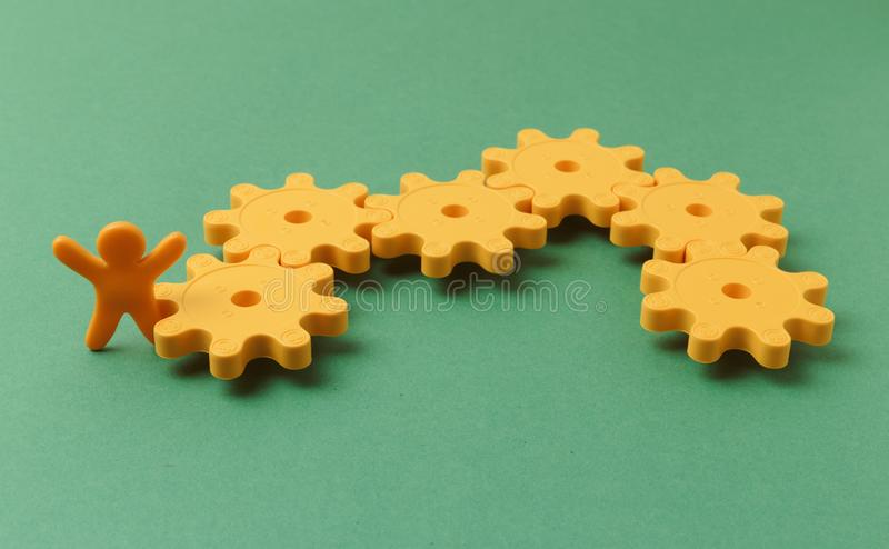 Yellow plastic gears. On a green background stock image