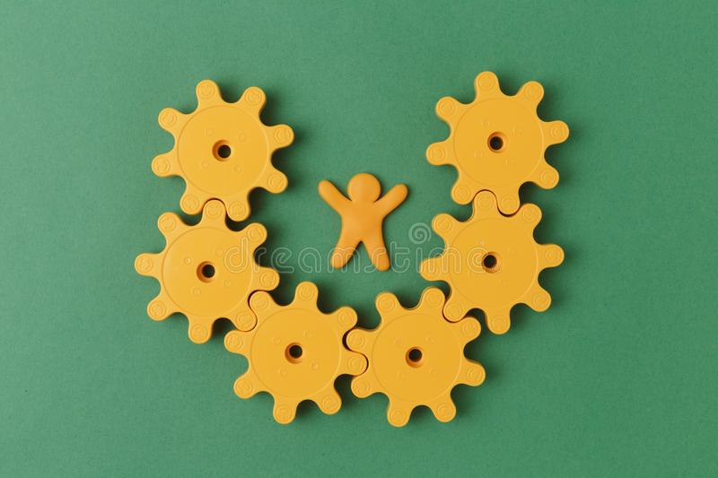 Yellow plastic gears. On green table royalty free stock image