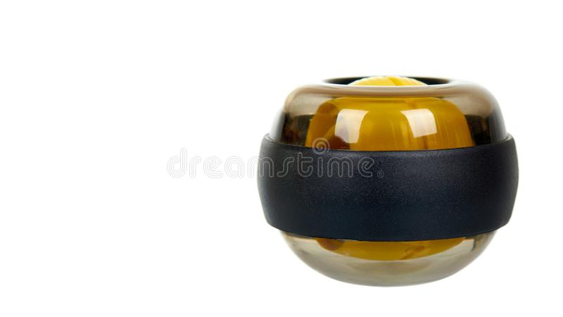 Yellow plastic gyroball. Exercise equipment for wrist. Sport tool. Isolated on white background. Copy space royalty free stock photography
