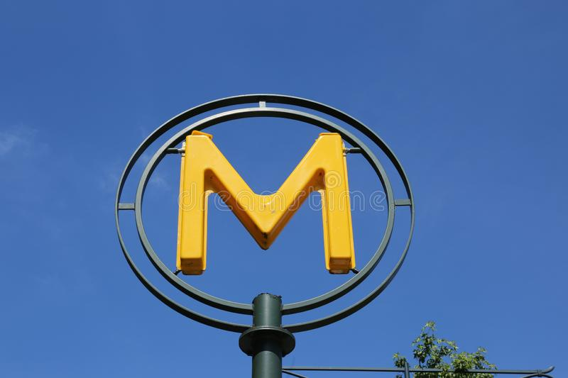 Yellow plastic letter M on a background of blue sky - sign of the subway in Paris in France stock images