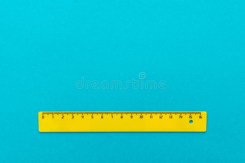 Yellow plastic ruler on the turquoise blue. Background stock photos