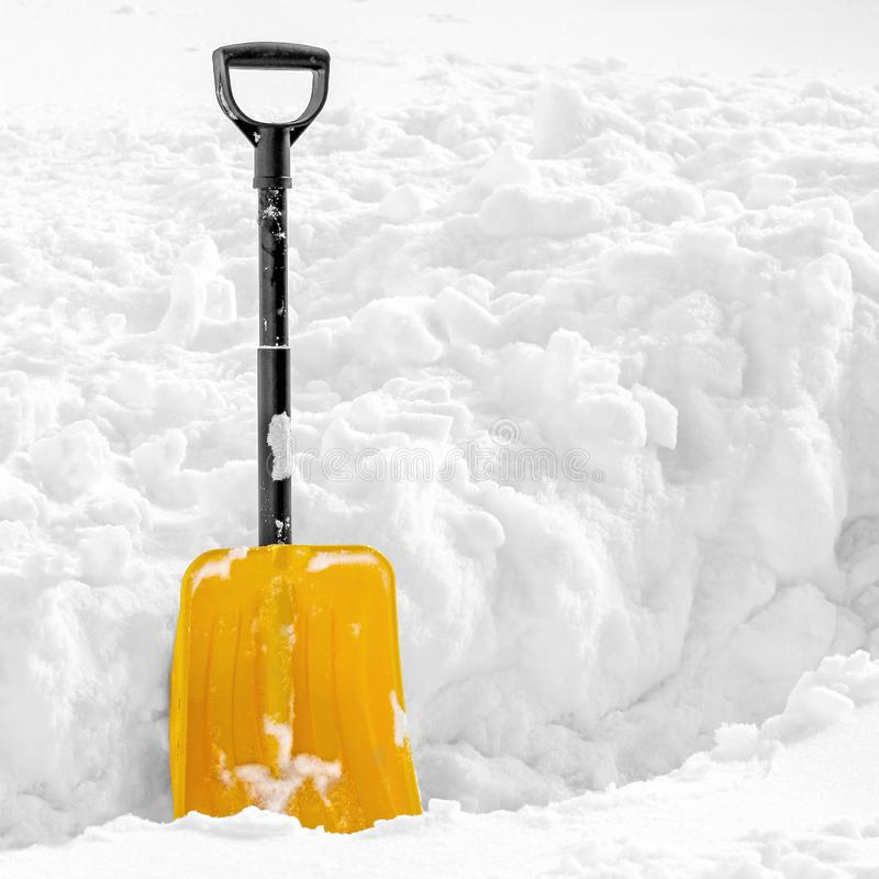 Yellow plastic shovel stuck in fluffy white snow in winter royalty free stock images