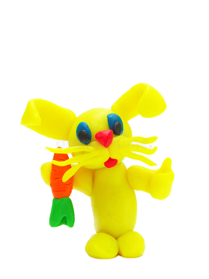 Yellow plasticine rabbit with carrot stock photography