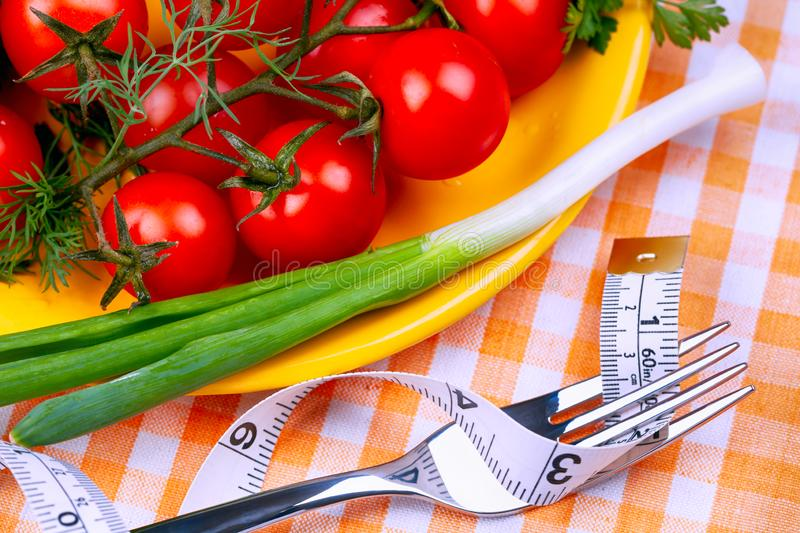Yellow plate with cherry tomatoes and green onion and fork with tape measure on checkered tablecloth. Close-up stock photos