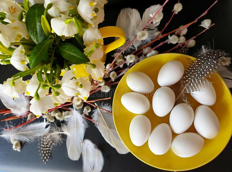 Eggs With Willow tree and  White Spring flower bouquet  still life green yellow red feathers down decoration easter yellow cu. Yellow plate and cup Eggs With royalty free stock image