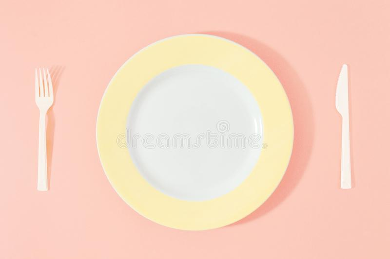 Yellow plate knife fork pink background Top view flat lay Diet m stock photo