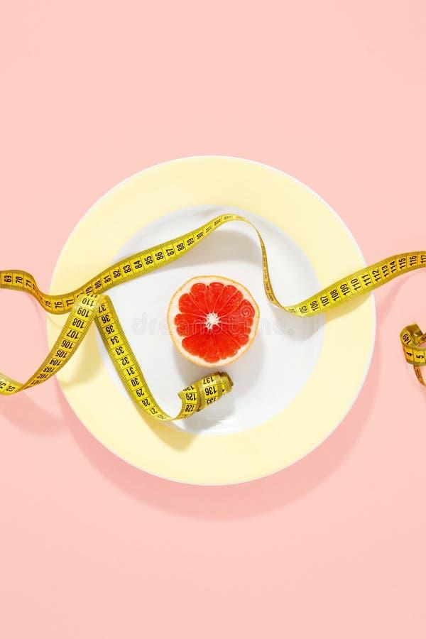 Yellow plate measuring tape half grapefruit pink background Top. Yellow plate with measuring tape and half grapefruit on pink background. Top view, flat lay stock photos