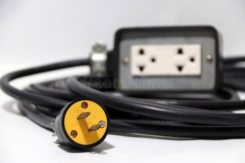 Yellow plug and out focus outlet with black cable on the white background. Used for electrical connection. royalty free stock image