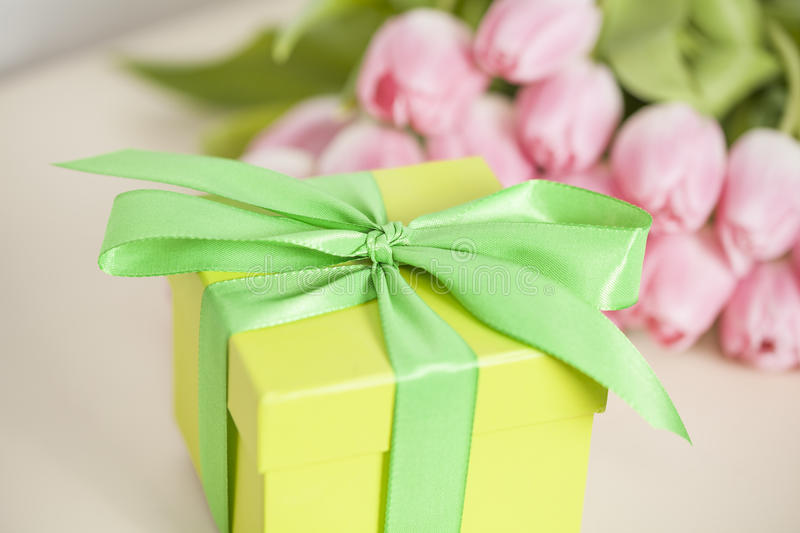 Yellow present and tulips. Yellow present and pink tulips stock photos