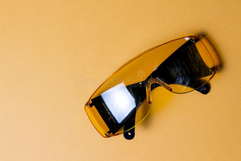 Yellow protective glasses on a yellow background. Accessor builder glasses for eye safety. stock image