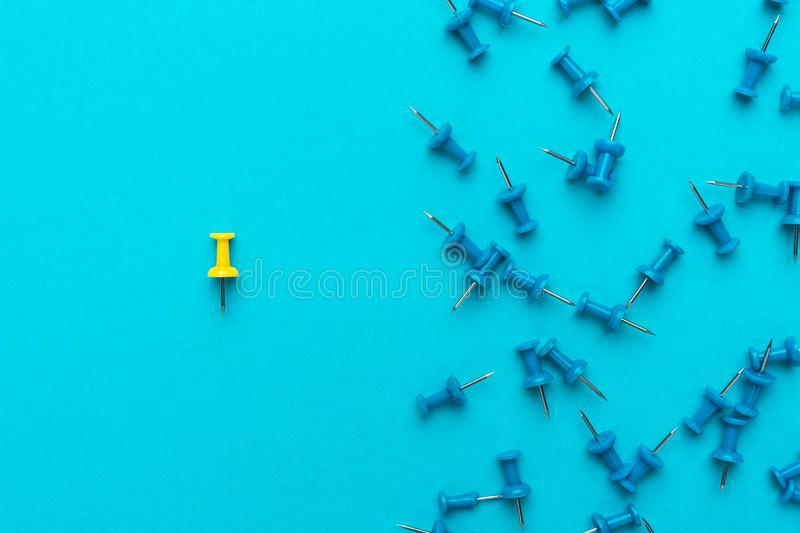 Yellow push pin out of the crowd concept over blue backgound royalty free stock photo