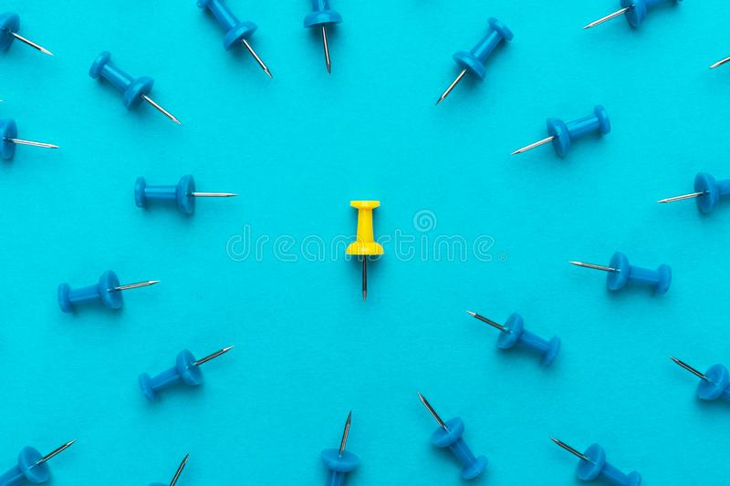 Yellow push pin out of the crowd conceptual photo of attack on person for views stock photos