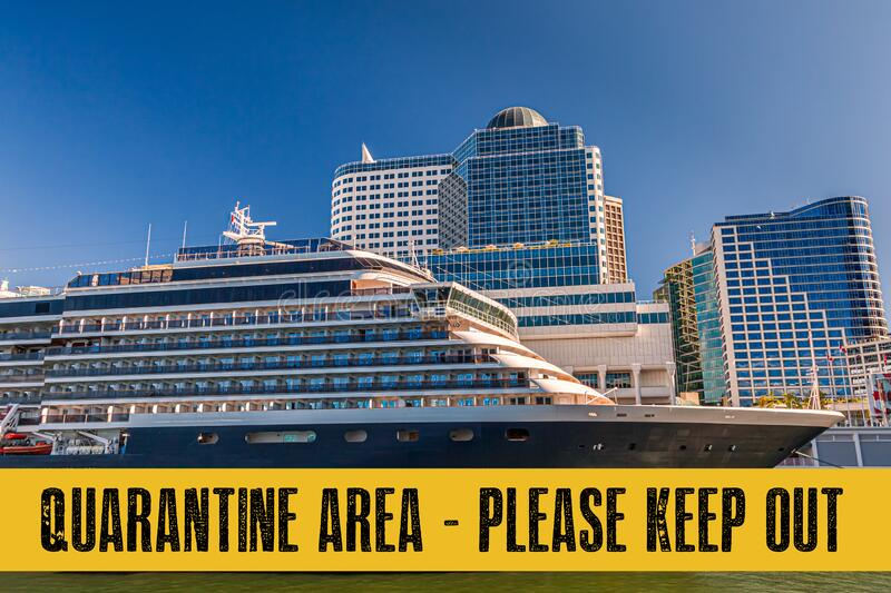 Yellow quarantine sign over a cruise ship at port stock images