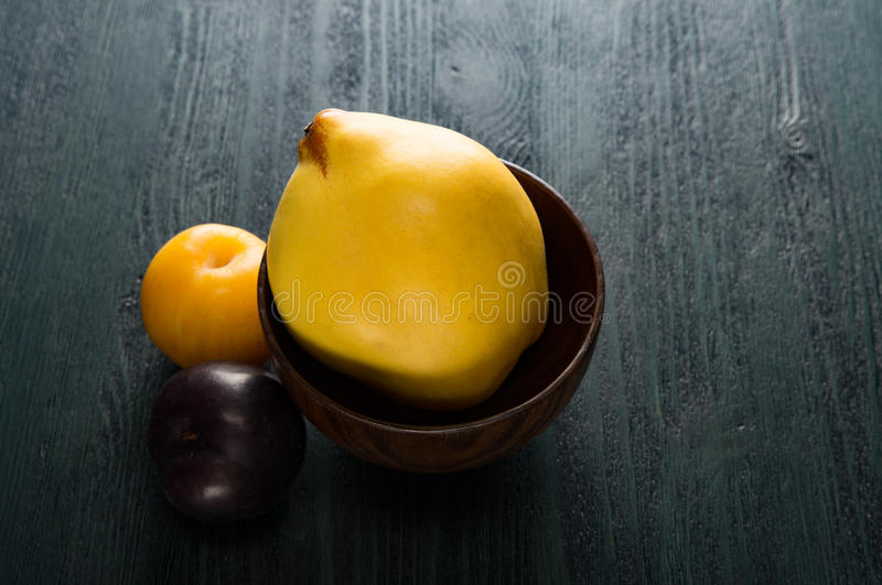 Yellow quince and plums in brown wooden bowl on the dark table royalty free stock photo