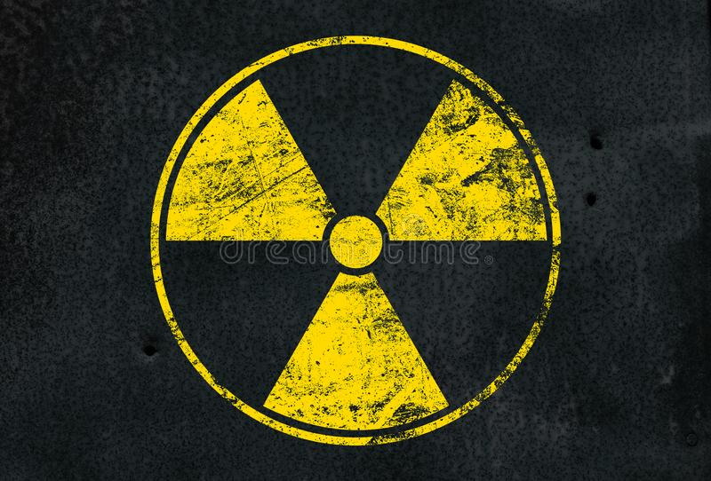 Yellow radioactive sign over black background. Yellow radioactive hazard warning sign painted over grunge black metal wall background with copy space royalty free stock photos