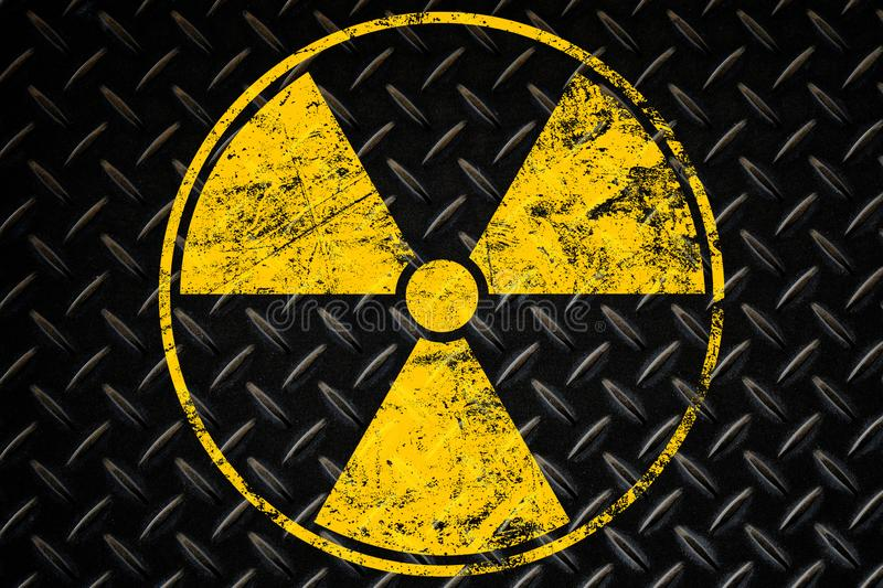 Yellow radioactive sign over black background. Yellow radioactive hazard warning sign painted over grunge black metal wall background with copy space royalty free stock photography