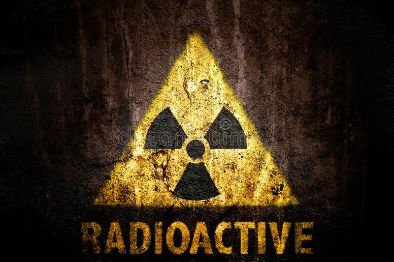 Radioactive: yellow radioactive ionizing radiation danger symbol with word radioactive painted below the sign. Yellow radioactive ionizing radiation danger royalty free stock photo