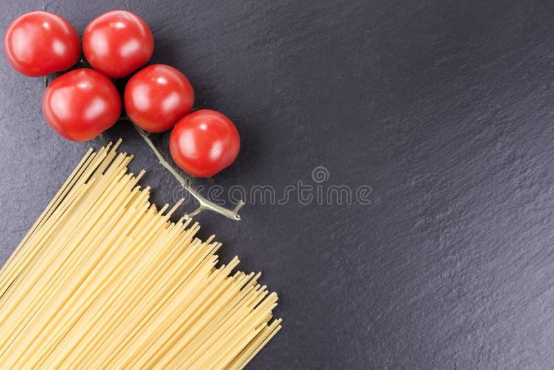 Yellow raw spaghetti and cherry tomatoes on black slate plate. Yellow long raw spaghetti and cherry tomatoes on black slate plate stock image