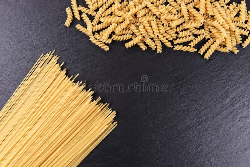 Yellow raw spaghetti and macaroni on black slate plate. Yellow long raw spaghetti and macaroni on black slate plate stock photography
