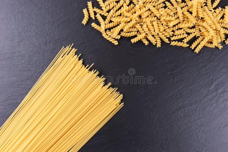 Yellow raw spaghetti and macaroni on black slate plate. Yellow long raw spaghetti and macaroni on black slate plate royalty free stock photography