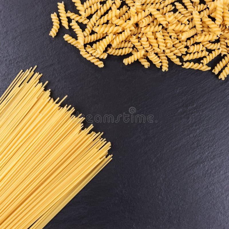 Yellow raw spaghetti and macaroni on black slate plate. Yellow long raw spaghetti and macaroni on black slate plate royalty free stock image