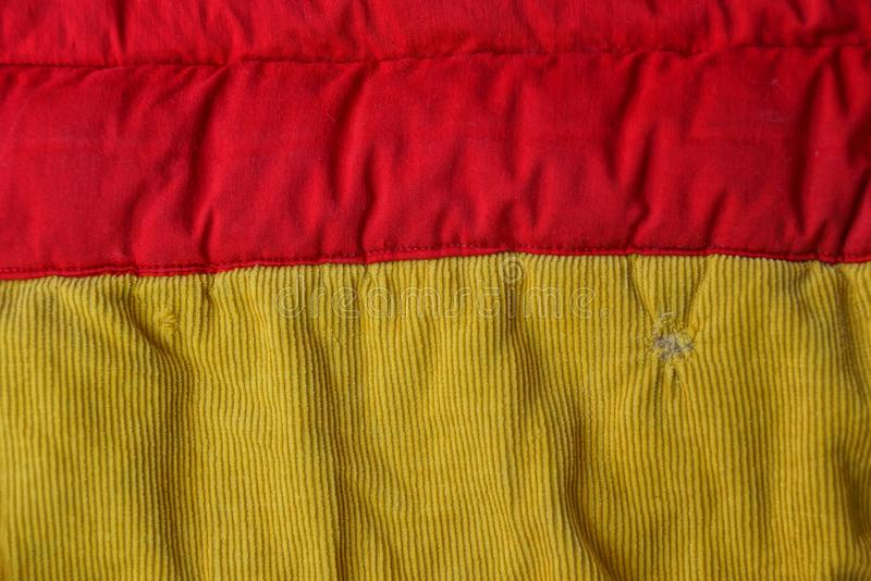 Yellow red background of fabric from a crumpled piece of fabric on clothes. Yellow red fabric texture from a crumpled piece of fabric on clothes stock photography