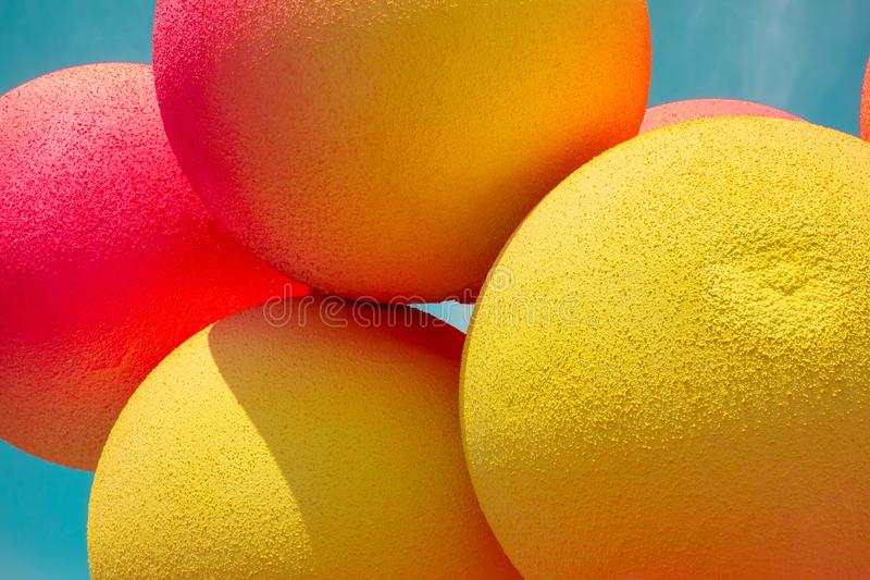 Yellow and red balls balloons on cloud sky background. Macro close up image. Vivid holiday poster with copy space. Sunny happy day. Concept royalty free stock photos