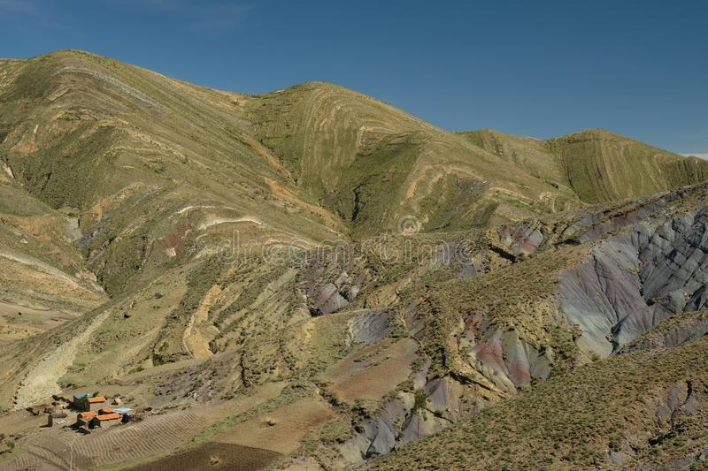 Streaked green and rainbow mountains in Maragua Crater. Bolivia with farm houses royalty free stock image